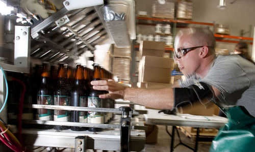 Steve Griffin  |  The Salt Lake Tribune Epic Brewery packaging supervisor, Nick Cleveland, removes bottles of beer from the bottling line and packages them at the Salt Lake City, Utah brewery on Wednesday.