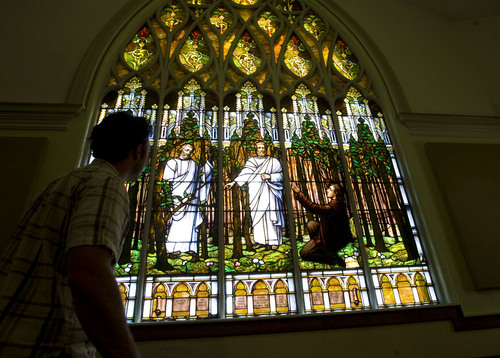 The Salt Lake Second Ward at 704 S. 500 E. shows a distinctive Gothic Revival style with a corner tower.  It's  stained-glass window of Joseph Smith's First Vision is awe inspiring.  Clayton Vance, a graduate student in architecture at Notre Dame looks at the window from inside the chapel.    Al Hartmann/The Salt Lake Tribune   7/12/2009