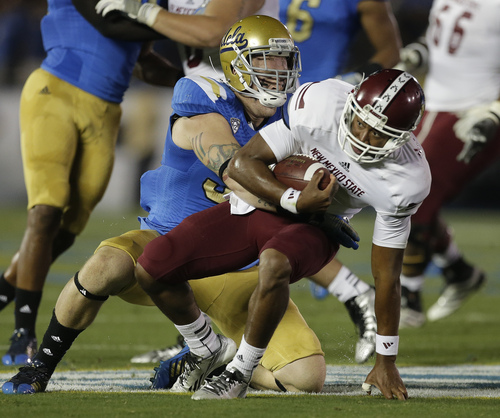 UCLA defensive end Cassius Marsh sacks New Mexico State quarterback King Davis III during the first half of an NCAA college football game Saturday, Sept. 21, 2013, in Pasadena, Calif. (AP Photo/Chris Carlson)