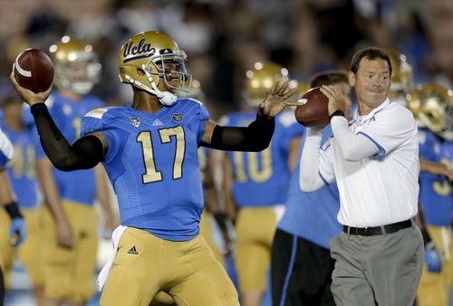 UCLA quarterback Brett Hundley, left, and coach Jim Mora warm up before an NCAA college football game against New Mexico State on Saturday, Sept. 21, 2013, in Pasadena, Calif. (AP Photo/Chris Carlson)