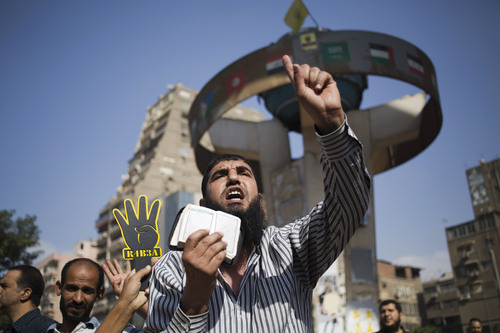 Supporters of Egypt's ousted President Mohammed Morsi chant slogans against Egyptian Defense Minister Gen. Abdel-Fattah el-Sissi and hold placards showing an open palm with four raised fingers, which has become a symbol of the Rabaah al-Adawiya mosque, where Morsi supporters had held a sit-in for weeks that was violently dispersed in August during a protest in Cairo, Egypt, Friday, Oct. 4, 2013. (AP Photo/Hassan Ammar)