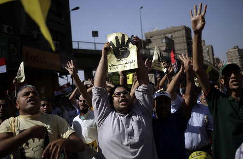 Supporters of Egypt's ousted President Mohammed Morsi chant slogans against Egyptian Defense Minister Gen. Abdel-Fattah el-Sissi and hold placards showing an open palm with four raised fingers, which has become a symbol of the Rabaah al-Adawiya mosque, where Morsi supporters had held a sit-in for weeks that was violently dispersed in August during a protest in Cairo, Egypt, Friday, Oct. 4, 2013. An Egyptian security official says gunmen have attacked an army convoy east of Cairo, killing two soldiers. The official says attackers opened fire at the convoy of mostly military trucks towing tanks and other armored vehicles on Friday morning on the road between the Suez Canal city of Ismailia and Cairo. (AP Photo/ Khalil Hamra)