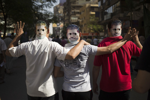 Supporters of Egypt's ousted President Mohammed Morsi wear masks with the former leader's likeness showing an open palm with four raised fingers, which has become a symbol of the Rabaah al-Adawiya mosque, where Morsi supporters had held a sit-in for weeks that was violently dispersed in August during a protest in Cairo, Egypt, Friday, Oct. 4, 2013.(AP Photo/Hassan Ammar)