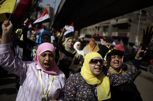 Supporters of Egypt's ousted President Mohammed Morsi chant slogans against Egyptian Defense Minister Gen. Abdel-Fattah el-Sissi and hold placards showing an open palm with four raised fingers, which has become a symbol of the Rabaah al-Adawiya mosque, where Morsi supporters had held a sit-in for weeks that was violently dispersed in August during a protest in Cairo, Egypt, Friday, Oct. 4, 2013. An Egyptian security official said gunmen attacked an army convoy east of Cairo. The official said attackers opened fire at the convoy of mostly military trucks towing tanks and other armored vehicles on Friday morning on the road between the Suez Canal city of Ismailia and Cairo. (AP Photo/ Khalil Hamra)