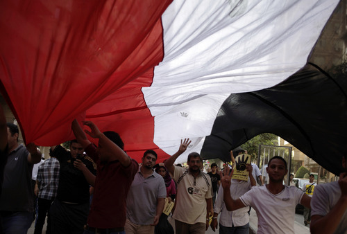 Supporters of Egypt's ousted President Mohammed Morsi chant slogans against Egyptian Defense Minister Gen. Abdel-Fattah el-Sissi while raising their open palms with four raised fingers, which has become a symbol of the Rabaah al-Adawiya mosque, where Morsi supporters had held a sit-in for weeks that was violently dispersed in August during a protest in Cairo, Egypt, Friday, Oct. 4, 2013. An Egyptian security official said gunmen attacked an army convoy east of Cairo. The official said attackers opened fire at the convoy of mostly military trucks towing tanks and other armored vehicles on Friday morning on the road between the Suez Canal city of Ismailia and Cairo. (AP Photo/ Khalil Hamra)