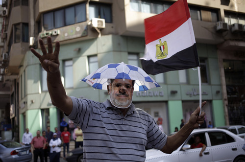Supporters of Egypt's ousted President Mohammed Morsi chant slogans against Egyptian Defense Minister Gen. Abdel-Fattah el-Sissi as he show an open palm with four raised fingers, which has become a symbol of the Rabaah al-Adawiya mosque, where Morsi supporters had held a sit-in for weeks that was violently dispersed in August during a protest in Cairo, Egypt, Friday, Oct. 4, 2013. An Egyptian security official said gunmen attacked an army convoy east of Cairo. The official said attackers opened fire at the convoy of mostly military trucks towing tanks and other armored vehicles on Friday morning on the road between the Suez Canal city of Ismailia and Cairo. (AP Photo/ Khalil Hamra)