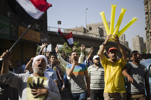 Supporters of Egypt's ousted President Mohammed Morsi chant slogans against Egyptian Defense Minister Gen. Abdel-Fattah el-Sissi and hold placards showing an open palm with four raised fingers, which has become a symbol of the Rabaah al-Adawiya mosque, where Morsi supporters had held a sit-in for weeks that was violently dispersed in August during a protest in Cairo, Egypt, Friday, Oct. 4, 2013.(AP Photo/Hassan Ammar)