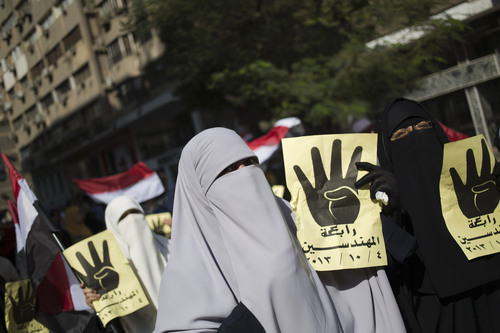 """Supporters of Egypt's ousted President Mohammed Morsi chant slogans against Egyptian Defense Minister Gen. Abdel-Fattah el-Sissi and hold placards showing an open palm with four raised fingers, which has become a symbol of the Rabaah al-Adawiya mosque, where Morsi supporters had held a sit-in for weeks that was violently dispersed in August during a protest in Cairo, Egypt, Friday, Oct. 4, 2013. Arabic on the placard reads, """"Rabaah, Mohandessin."""" (AP Photo/Hassan Ammar)"""