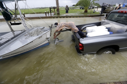 C.J. Johnson pulls a shrimp boat out of the water, in anticipation of Tropical Storm Karen, at Myrtle Grove Marina in Plaquemines Parish, La., Friday, Oct. 4, 2013.  National Hurricane Center forecasters expect Karen to be near the central Gulf Coast on Saturday as a weak hurricane or tropical storm. Along with strong winds, the storm was expected to produce rainfall of 3 to 6 inches through Sunday night, with isolated totals up to 10 inches possible. Forecast tracks showed it possibly brushing, or crossing, the southeast Louisiana coast before veering eastward toward south Alabama and the Florida panhandle. (AP Photo/Gerald Herbert)