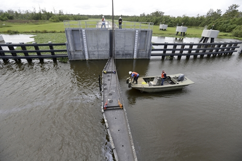Workers lower a flood gate into Hero Canal, as part of the hurricane protection system protecting the greater New Orleans area, in anticipation of Tropical Storm Karen, in Belle Chasse, La., Friday, Oct. 4, 2013.  National Hurricane Center forecasters expect Karen to be near the central Gulf Coast on Saturday as a weak hurricane or tropical storm. Along with strong winds, the storm was expected to produce rainfall of 3 to 6 inches through Sunday night, with isolated totals up to 10 inches possible. Forecast tracks showed it possibly brushing, or crossing, the southeast Louisiana coast before veering eastward toward south Alabama and the Florida panhandle. (AP Photo/Gerald Herbert)