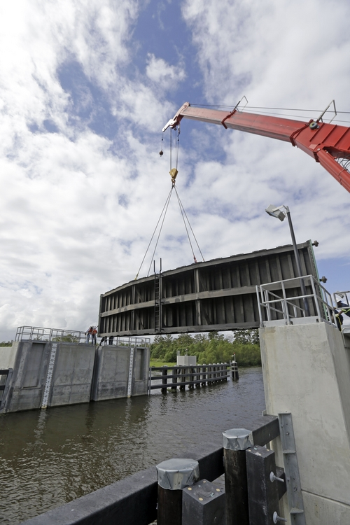 A crane lowers a flood gate into Hero Canal, as part of the hurricane protection system protecting the greater New Orleans area, in anticipation of Tropical Storm Karen, in Belle Chasse, La., Friday, Oct. 4, 2013.  National Hurricane Center forecasters expect Karen to be near the central Gulf Coast on Saturday as a weak hurricane or tropical storm. Along with strong winds, the storm was expected to produce rainfall of 3 to 6 inches through Sunday night, with isolated totals up to 10 inches possible. Forecast tracks showed it possibly brushing, or crossing, the southeast Louisiana coast before veering eastward toward south Alabama and the Florida panhandle. (AP Photo/Gerald Herbert)