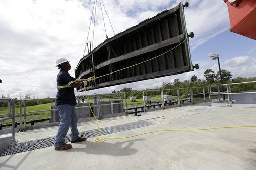 A worker guides a flood gate as a crane lowers it into into Hero Canal, as part of the hurricane protection system protecting the greater New Orleans area, in anticipation of Tropical Storm Karen, in Belle Chasse, La., Friday, Oct. 4, 2013.  National Hurricane Center forecasters expect Karen to be near the central Gulf Coast on Saturday as a weak hurricane or tropical storm. Along with strong winds, the storm was expected to produce rainfall of 3 to 6 inches through Sunday night, with isolated totals up to 10 inches possible. Forecast tracks showed it possibly brushing, or crossing, the southeast Louisiana coast before veering eastward toward south Alabama and the Florida panhandle. (AP Photo/Gerald Herbert)