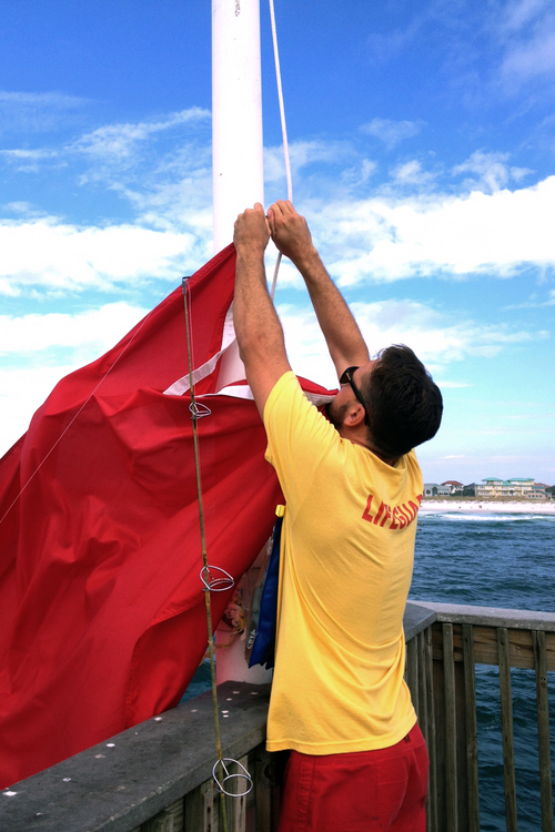 A lifeguard hangs a red flag indicating dangerous surf conditions on Friday, Oct. 4, 2013., at Pensacola Beach, Fla. Preparations were continuing in states east of Louisiana as the forecast for Tropical Storm Karen continued to indicate an eventual move to the northeast. (AP Photo/The Pensacola News Journal, Kim Blair)