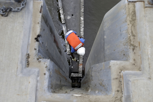 A worker secures a flood gate after a crane lowered it into Hero Canal, as part of the hurricane protection system protecting the greater New Orleans area, in anticipation of Tropical Storm Karen, in Belle Chasse, La., Friday, Oct. 4, 2013. National Hurricane Center forecasters expect Karen to be near the central Gulf Coast on Saturday as a weak hurricane or tropical storm. (AP Photo/Gerald Herbert)