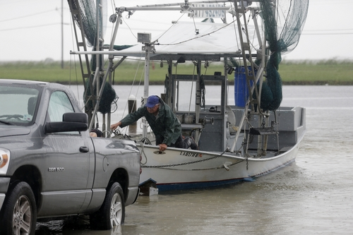 Tony Danos secures a shrimp boat to pull it out of the water, in anticipation of Tropical Storm Karen, at Myrtle Grove Marina in Plaquemines Parish, La., Friday, Oct. 4, 2013.  National Hurricane Center forecasters expect Karen to be near the central Gulf Coast on Saturday as a weak hurricane or tropical storm. Along with strong winds, the storm was expected to produce rainfall of 3 to 6 inches through Sunday night, with isolated totals up to 10 inches possible. Forecast tracks showed it possibly brushing, or crossing, the southeast Louisiana coast before veering eastward toward south Alabama and the Florida panhandle. (AP Photo/Gerald Herbert)