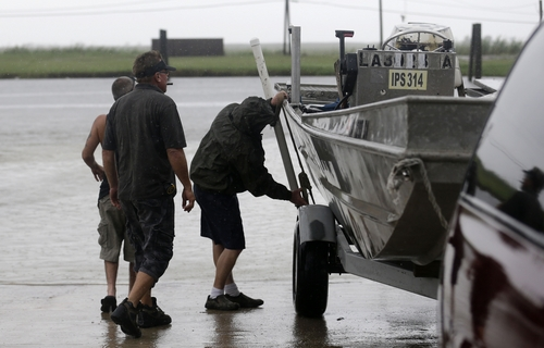 People put a boat in the water to secure their fishing camp in anticipation of Tropical Storm Karen, at Myrtle Grove Marina in Plaquemines Parish, La., Friday, Oct. 4, 2013.  National Hurricane Center forecasters expect Karen to be near the central Gulf Coast on Saturday as a weak hurricane or tropical storm. Along with strong winds, the storm was expected to produce rainfall of 3 to 6 inches through Sunday night, with isolated totals up to 10 inches possible. Forecast tracks showed it possibly brushing, or crossing, the southeast Louisiana coast before veering eastward toward south Alabama and the Florida panhandle. (AP Photo/Gerald Herbert)