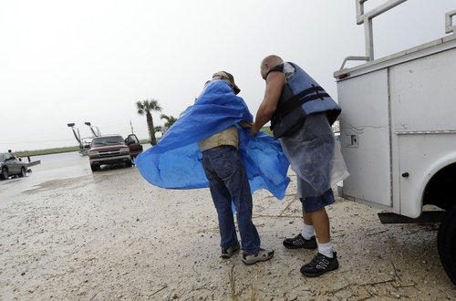 Brad Robertson, right, secures a poncho to Ed Gomez as they prepare to boat out to their fishing camp to board it up, in anticipation of Tropical Storm Karen, at Myrtle Grove Marina in Plaquemines Parish, La., Friday, Oct. 4, 2013.  National Hurricane Center forecasters expect Karen to be near the central Gulf Coast on Saturday as a weak hurricane or tropical storm. Along with strong winds, the storm was expected to produce rainfall of 3 to 6 inches through Sunday night, with isolated totals up to 10 inches possible. Forecast tracks showed it possibly brushing, or crossing, the southeast Louisiana coast before veering eastward toward south Alabama and the Florida panhandle. (AP Photo/Gerald Herbert)