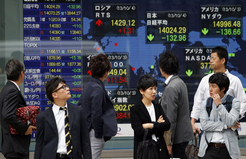 Passers-by watch an electronic stock board of a securities firm in Tokyo, Friday, Oct. 4, 2013. Uncertainty about how long the partial shutdown of the U.S. government will last kept Asian stock markets on edge Friday. (AP Photo/Koji Sasahara)