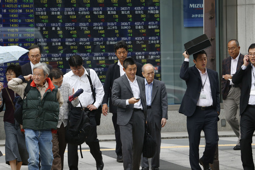 People walk by an electronic stock board of a securities firm in Tokyo, Friday, Oct. 4, 2013. Uncertainty about how long the partial shutdown of the U.S. government will last kept Asian stock markets on edge Friday. (AP Photo/Koji Sasahara)