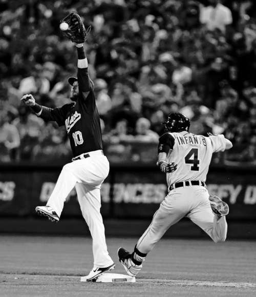 Detroit Tigers' Omar Infante beats the throw to Oakland Athletics first baseman Daric Barton in the fourth inning of Game 1 of the American League baseball division series in Oakland, Calif., Friday, Oct. 4, 2013. (AP Photo/Marcio Jose Sanchez)