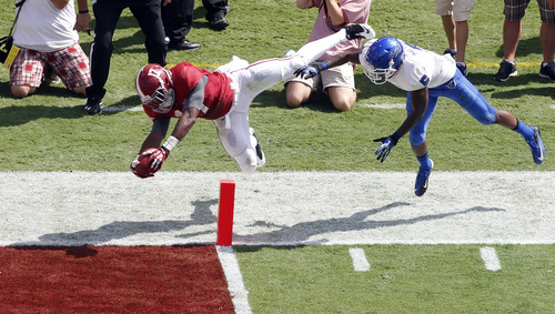 Alabama running back Kenyan Drake (17) dives over the goal line past Georgia State cornerback Demarius Matthews (5) for a touchdown in the first half of an NCAA college football game on Saturday, Oct. 5, 2013, in Tuscaloosa, Ala. (AP Photo/Butch Dill)