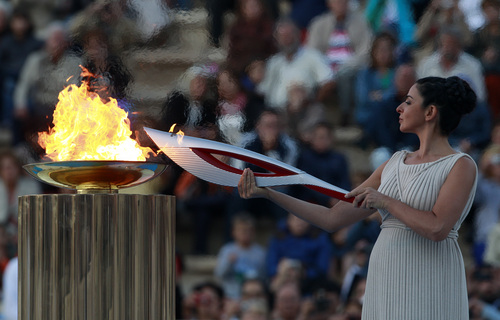 Actress Ino Menegaki, playing the role of  high priestess, lights the torch with the Olympic Flame during a handover ceremony in Athens' Panathinaiko Stadium, on Saturday, Oct. 5, 2013. The Olympic flame has been handed to organizers of the Sochi Winter Olympics in a ceremony at the site of the first modern summer games. After a seven-day run through Greece, the flame will cover 40,000 miles on Russian soil. The record-setting relay will start on Monday in Moscow and finish in Sochi on Feb. 7, the opening day of the games. (AP Photo/Kostas Tsironis)