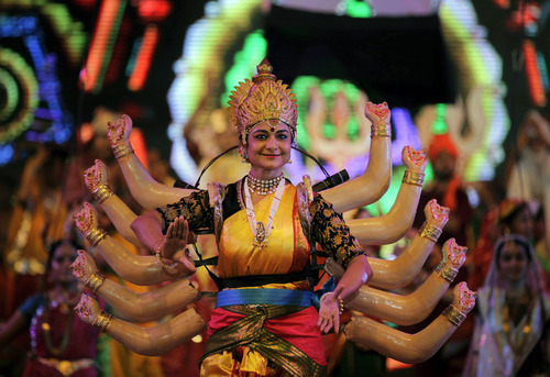 In this Friday, Oct. 4, 2013 photo, an Indian artist performs during the grand rehearsal for Navratri celebrations in Ahmadabad, India. Feasting and fasting takes over normal life for millions of Hindus during Navratri, the festival of nine nights. (AP Photo/Ajit Solanki)