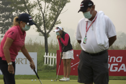 Golfers wear masks as they practice putting on a hazy morning for the third round of the Reignwood LPGA Classic golf tournament at Pine Valley Golf Club on the outskirts of Beijing, China, Saturday, Oct. 5, 2013. (AP Photo/Alexander F. Yuan)