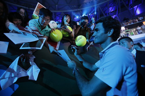 Roger Federer of Switzerland gives his autographs to fans during a fan meeting event ahead of the Shanghai Masters at Qizhon Tennis Center in Shanghai, China, Saturday, Oct. 5, 2013. (AP Photo/Eugene Hoshiko)