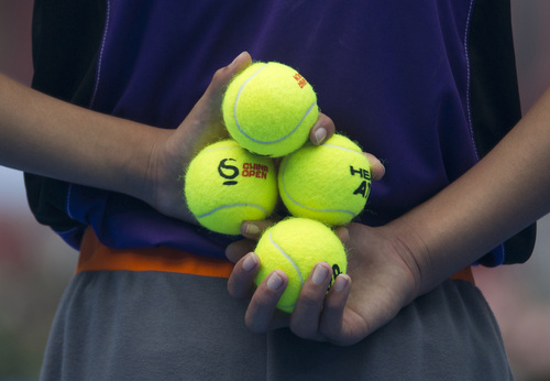 A ball boy holds tennis balls before the semifinal match between Rafael Nadal of Spain and Tomas Berdych of the Czech Republic at the China Open tennis tournament at the National Tennis Stadium in Beijing, China Saturday, Oct. 5, 2013. (AP Photo/Andy Wong)