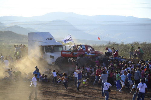 In this Saturday, Oct. 5, 2013, photo, people flee as an out-of-control monster truck plows through a crowd of spectators at an air show in Chihuahua, Mexico. According to authorities, the accident killed at least eight people and hurt at least 80 others, dozens seriously. (AP Photo/Courtesy El Diario de Chihuahua)