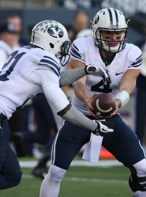 Leah Hogsten | The Salt Lake Tribune Brigham Young Cougars quarterback Taysom Hill (4) hands off to Brigham Young Cougars running back Jamaal Williams (21). Brigham Young University Cougars lead 17-7 at the half during their matchup against  Utah State University Aggies, Friday, October 4, 2013 in Logan.