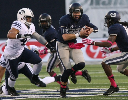 Leah Hogsten | The Salt Lake Tribune Utah State Aggies quarterback Craig Harrison (12) comes in for the game after Aggies quarterback Chuckie Keeton (16) is carted off the field with a knee injury.  Brigham Young University Cougars lead 17-7 after the first half during their matchup against  Utah State University Aggies Friday, October 4, 2013 in Logan.