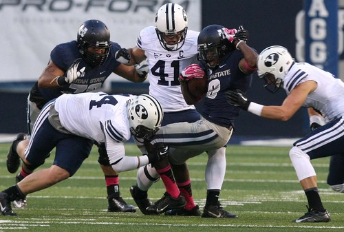 Leah Hogsten | The Salt Lake Tribune Utah State Aggies wide receiver Travis Reynolds (8) is brought down by Brigham Young Cougars defensive lineman Remington Peck (44).  Brigham Young University Cougars lead 17-7 after the first half during their matchup against  Utah State University Aggies Friday, October 4, 2013 in Logan.
