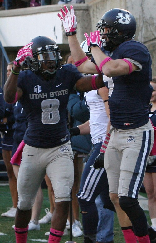 Leah Hogsten | The Salt Lake Tribune Utah State Aggies wide receiver Travis Reynolds (8) celebrates teammate Utah State Aggies wide receiver Travis Van Leeuwen's (7) touchdown. Brigham Young University Cougars lead 10-7 after the first quarter during their matchup against  Utah State University Aggies  Friday, October 4, 2013 in Logan.