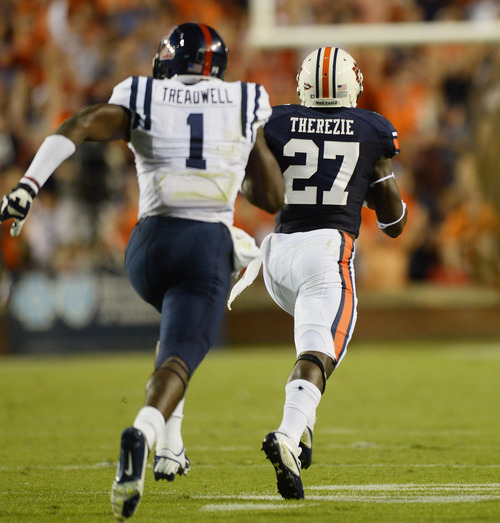 Auburn defender Robenson Therezie returns an interception for a touchdown during the first half of an NCAA college football game against Mississippi on Saturday, Oct. 5, 2013, in Auburn, Ala. (AP Photo/Todd J. Van Emst)