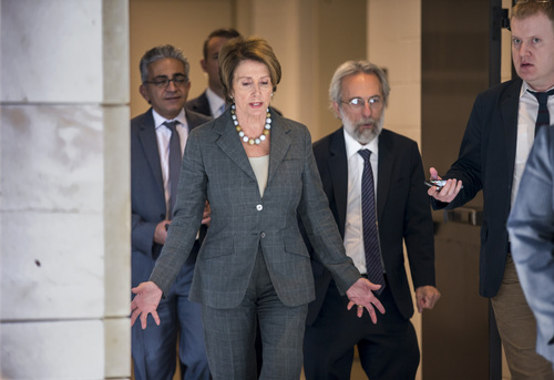 """House Minority Leader Nancy Pelosi, D-Calif., center, walks through the Capitol with her staff on the way to a news conference at the U.S. Capitol in Washington, Saturday, Oct. 5, 2013. There is no sign of progress towards ending the impasse that has idled 800,000 federal workers and curbed services around the country. """"This isn't some damn game,"""" House Speaker John Boehner, R-Ohio, has said as the White House and Democrats held to their position of agreeing to negotiate only after the government is reopened and the $16.7 trillion debt limit raised. (AP Photo/J. Scott Applewhite)"""