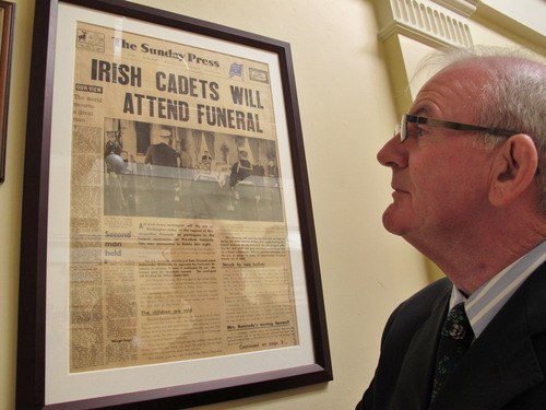 "ADVANCE FOR USE SATURDAY, OCT. 5, 2013 AND THEREAFTER - In this July 16, 2013 photo, former cadet Jim Sreenan looks at a newspaper from 50 years ago in The Curragh military camp in County Kildare, Ireland. The night before being flown to Washington, cadet Sreenan remembers the lights snapping on during the movie ""Genghis Khan"" and someone bellowing, ""All cadets report back to base."" (AP Photo/Helen O'Neill)"