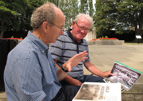 ADVANCE FOR USE SATURDAY, OCT. 5, 2013 AND THEREAFTER - In this July 17, 2013 photo, former cadets Peter McMahon, left, and Hugh O'Donnell look at newspaper clippings from 50 years ago at the Arbour Hill military cemetery in Dublin, Ireland. In a June 1963 wreath-laying ceremony here, U.S. President John F. Kennedy witnessed a special ceremonial drill for the dead, performed by Irish cadets. The drill so captivated him that his widow, Jacqueline Kennedy, asked that the next class of cadets, which included McMahon and O'Donnell, perform the same drill and be the honor guard at his funeral. (AP Photo/Helen O'Neill)