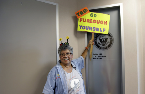 Leonor Ramus holds a sign at the door to the  San Antonio office of U.S. Sen. Ted Cruz, R-Texas, as she helps protest for federal workers idled by the government shutdown, Thursday, Oct. 3, 2013, in San Antonio. (AP Photo/Eric Gay)