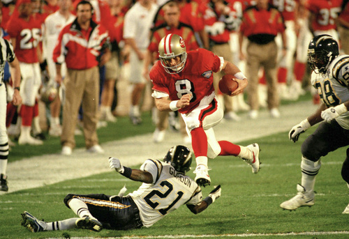 FILE - In this Jan. 29, 1995, file photo, San Francisco 49ers' quarterback Steve Young (8) runs over San Diego's Darrien Gordon (21) for a first down during the first quarter of Super Bowl XXIX at Joe Robbie Stadium in Miami. The 49ers are looking to win their sixth title when they take on the Baltimore Ravens in NFL football's Super Bowl XLVII on Sunday in New Orleans.  (AP Photo/Andrew Innerarity, File)