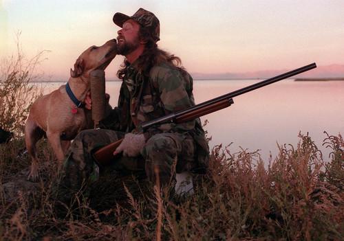    Tribune file photo  Gauge the Labarador licks Les Christensen's face while duck hunting at Farmington Bay.