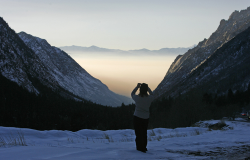 Kim Atno stops to take a picture of the Salt Lake Valley from Little Cottonwood Canyon Road, on her way home from Skiing at Alta. Rick Egan, The Salt Lake Tribune