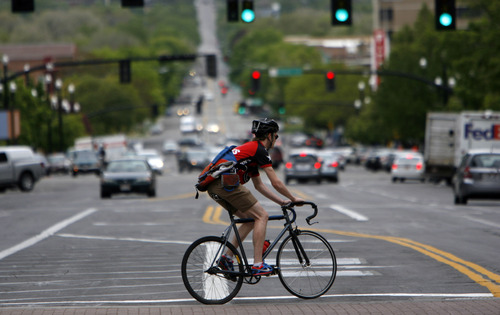 Francisco Kjolseth     The Salt Lake Tribune A bicyclist peddles through Salt Lake City downtown traffic on April 30, 2012. Cyclists who violate the rules of the road can be cited.