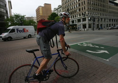 Kim Raff   The Salt Lake Tribune A J.J. Merrill rides a bicycle down 200 South in downtown Salt Lake City, Utah on April 30, 2012.