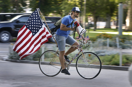 """Scott Sommerdorf      The Salt Lake Tribune Jack Lasley rides around announcing the Bicycle Ambassadors' July ride with the theme """"MERICA"""" in Salt Lake City, Saturday, July 13, 2013."""