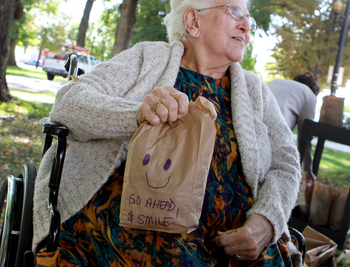 Keith Johnson | The Salt Lake Tribune   Wentworth at Willow Creek Assisted Living Center resident Colleen Hoopes holds a sack lunch decorated with kind words while she and other Willow Creek residents pass out lunches at Pioneer Park Tuesday, Oct. 8, 2013, in Salt Lake City.