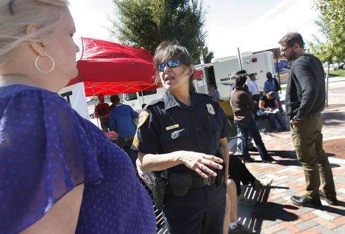 Scott Sommerdorf      The Salt Lake Tribune SLCPD Sgt/ Michelle Ross, center, speaks with an outreach worker near the temporary homeless outreach center set up on 500 West between 200 S and 300 S, Wednesday, September 18, 2013.