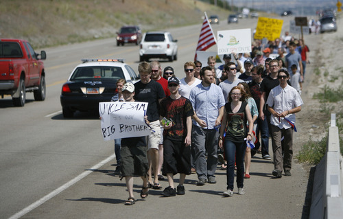 Francisco Kjolseth  |  The Salt Lake Tribune Opponents of the NSA Data Center protest the center on the 4th of July, by marching up to the Intersection of NSA Data Center access road and Redwood Road across from Camp Williams.