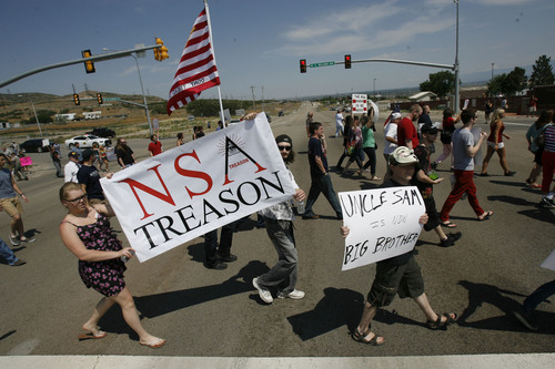 Francisco Kjolseth  |  The Salt Lake Tribune Brandon Otterstron, center, of Clearfield joins others to protest the new NSA Data Center along Redwood road across from Camp Williams on the 4th of July.